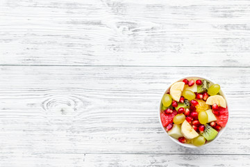 Fruit diet concept. Fruit salad with apple, kiwi and pomegranate in bowl on white wooden background top view space for text