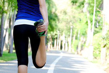 body beautiful of woman running on road in the park  which runner athletic by running shoes and she was stretching her thigh muscles. Health and sport concept background,
