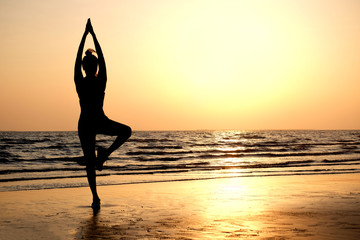 Morning of a new day,  woman playing yoga and stretching muscles on the beach sunlight in morning. Health concept.