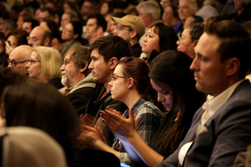Audience members listen as former Starbucks CEO Howard Schultz speaks during his book tour in Seattle, Washington