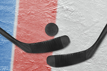 Blue and red lines on the ice, and two hockey sticks with the puck