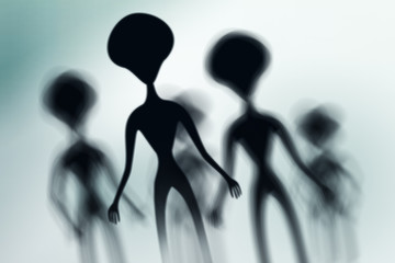 Silhouettes of spooky aliens and bright light on behind them