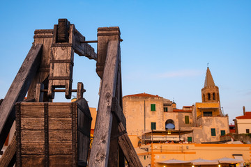 Alghero, Sardinia, Italy - Summer sunset view of the Alghero old town quarter with historic defense walls, fortifications and catapult construction