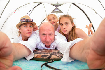 Family, mom, dad and two children take pictures of themselves on vacation inside a spacious bright tent