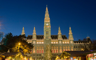 Vienna, Austria, town hall building in the evening. The building is built in the neo-Gothic style with a symmetrical main facade. The main facade of the town hall has 5 towers.