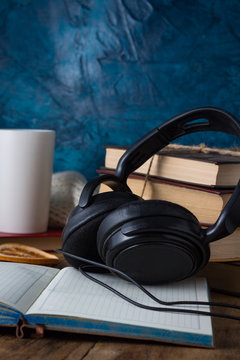 Books are stacked, Headphones, White Cup, open Diary on a wooden background. The Concept of Audio Books
