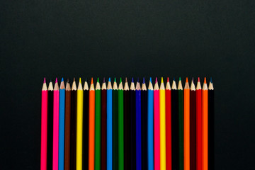 Colored pencils lined up in a row on a black background. Flat lay, top view