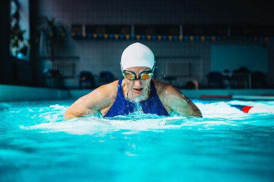 Professional woman swimmer swim using breaststroke technique on the dark background