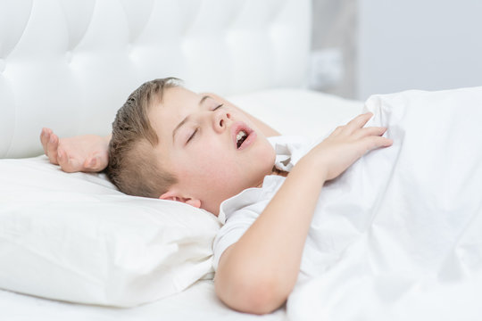 Boy is sleeping on the bed with his mouth open, snoring