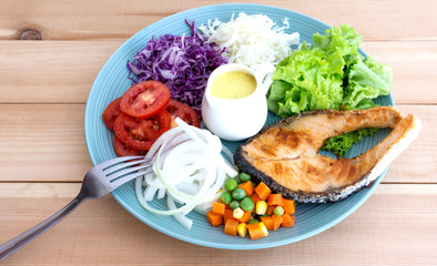 Salmon Salad in Plate on wood floor background, Healthy salad diet food concept, Top view.
