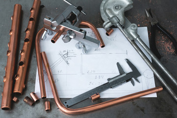 Brass pipes, pipe bender, pipe rammer tool and a layout drafts on a fitter workbench.