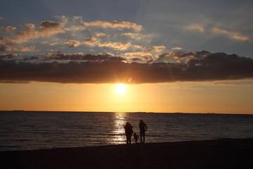 silhouettes d'une famille sur la plage au coucher du soleil