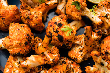 Tandoori Gobi / Roasted cauliflower Tikka is a dry dish made by roasting Cauliflowers in Oven/Tandoor. It's  popular starter food from India. served with ketchup. selective focus