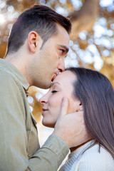 Man kisses in the forehead of his girlfriend in a public park