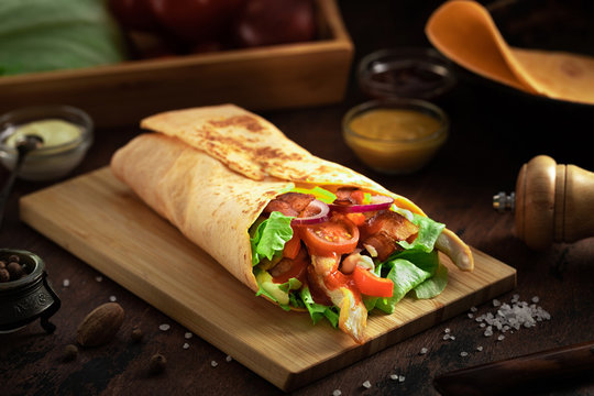 Mexican burrito wrap with corn tortilla, chicken meat and vegetables on dark rustic background. Chicken grilled shawarma with bacon, pita bread, tomatos and salad and different sauces.