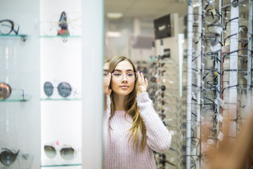 Health care, eyesight and vision concept. Young happy woman choosing glasses at optics store