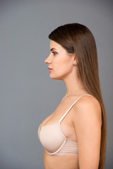 Canvas Prints Textures Close up portrait of beautiful brunette women with a slim figure in beige bra. Model snaps in the studio on gray background
