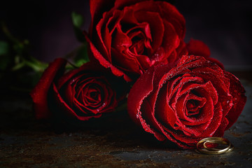 Red roses with dark background with wedding ring