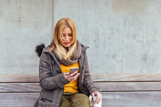 Portrait of blonde woman using her mobile phone