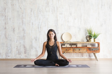 Slim beautiful young woman in a black tight suit meditates sitting in the lotus position with eyes closed against a background of wooden vintage consoles and concrete wall