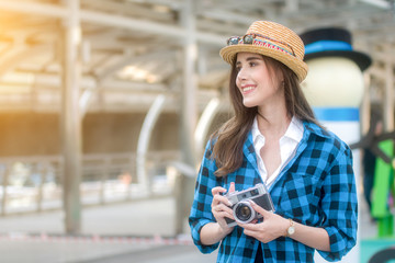 Young beautiful Asian backpack traveler woman using compact camera and smile, looking at copy space.
