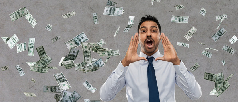 business, stress and people concept - indian businessman shouting over money rain on grey background