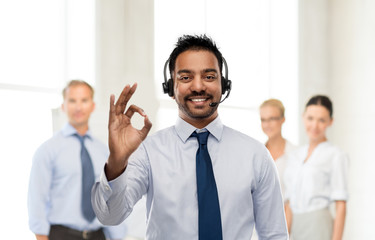 business, customer service and people concept - smiling indian businessman or helpline operator in headset over colleagues on background showing ok gesture