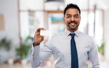 business and people concept - smiling indian businessman holding visiting card over office background
