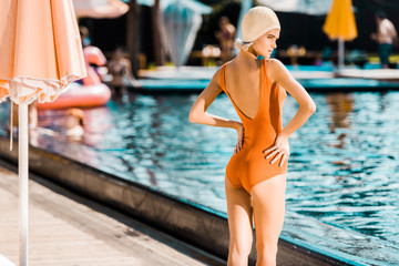rear view of stylish pin up girl in orange swimsuit posing at poolside