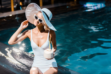 pin up girl in swimsuit, sunglasses and hat holding green coconut at poolside