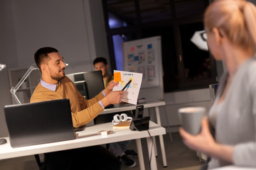 business, deadline and people concept - man showing papers to colleague late at night office