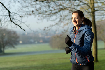 Woman On Early Morning Winter Run In Park Keeping Fit Listening To Music Through Earphones