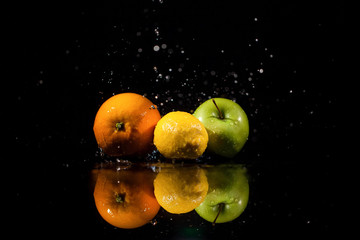 The apple,orange and lemon   stand on the black background