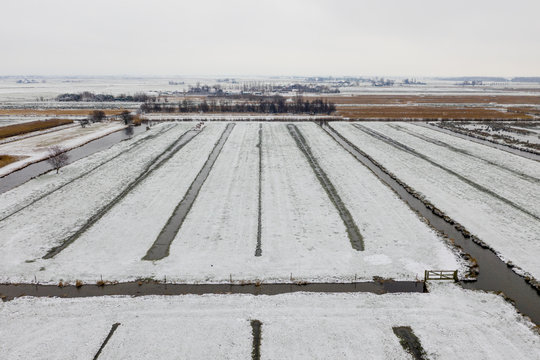 Agricultural fields covered with a thin layer of snow. Tiny canals used for water management are visible in this landscape picture from the sky.