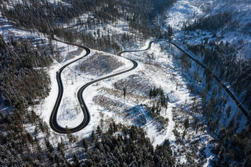 Curvy windy road in snow covered forest, top down aerial view. Winter landscape.