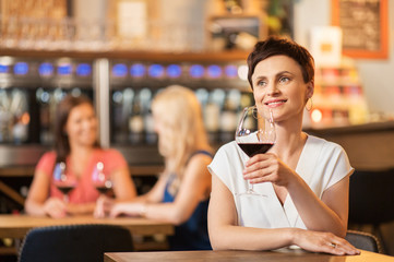 people, celebration and lifestyle concept - happy middle aged woman drinking red wine and talking at restaurant or bar