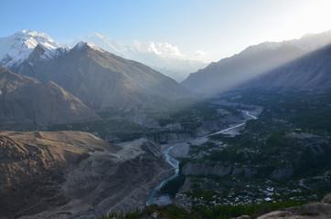 パキスタンのフンザの絶景 美しい山と新緑と街並み 高台から撮影した全体写真  朝日が差し込む瞬間