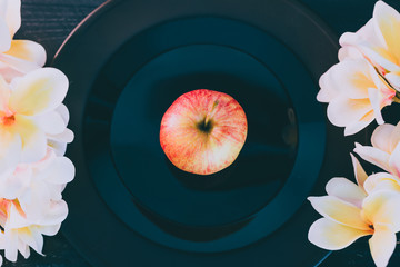 one apple on black plate on dark background and white flowers around it
