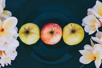 apples on black plate on dark background and white flowers around them