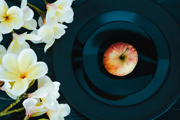 one apple on black plate on dark background and flowers