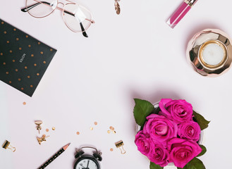 Creative frame with cute feminine accessories, stationery and pink roses