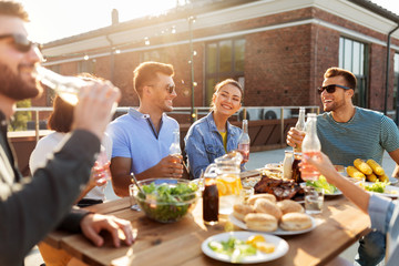 leisure and people concept - happy friends with drinks having barbecue party on rooftop