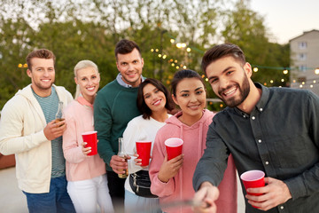 leisure and people concept - happy friends with drinks taking selfie at rooftop party in summer