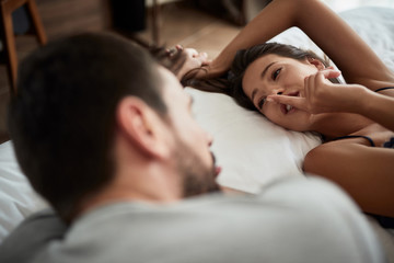 Intimate couple during foreplay in bed.
