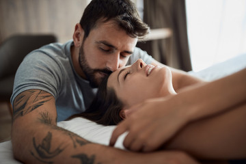Sexy men and woman being intimate in bed.