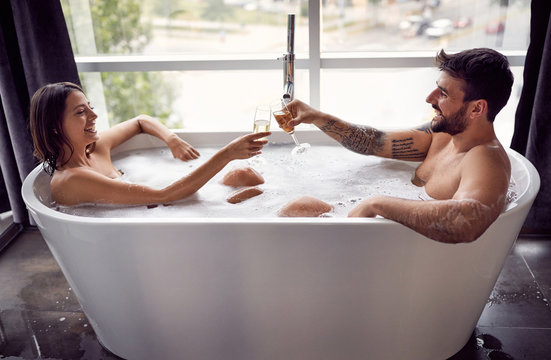 Smiling man and woman have fun together in the bathtub and drinking champagne.