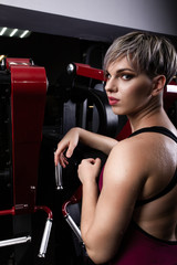 Beautiful sport girl is engaged on a simulator in the gym. Pretty girl with the beautiful tightened figure. Fitness girl in the gym