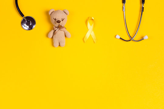 Childhood Cancer Awareness Yellow Ribbon with toy bear and stethoscope on yellow background with copy space.