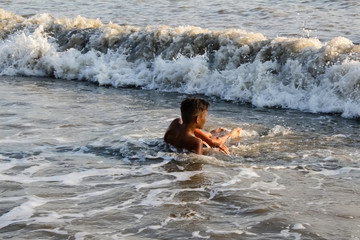 boy teenager lies on the seashore his washes sea foam and waves