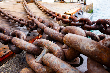 Close up of old rusty chain, industrial port with chainss, crane background out of focus, sunny day, industrial concept